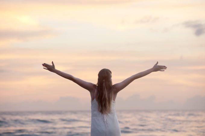 image femme bras ouverts face océan pexels