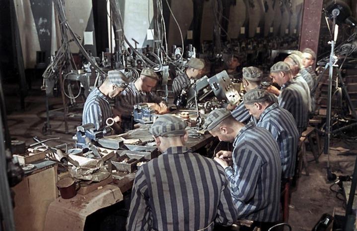 Dix déportés travaillant au montage des fusées V2 à Dora. Photo en couleur prise par Walter Frentz, photographe officiel, pour Albert Speer, ministre de l'armement, mars-juillet 1944. Une photographie de propagande qui ne témoigne en aucune façon de l'atroce condition des travailleurs forcés de l'usine de construction du Mittelwerk, au camp Mittelbau-Dora.