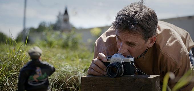 image steve carell allongé dans l'herbe avec un appareil photo bienvenue à marwen